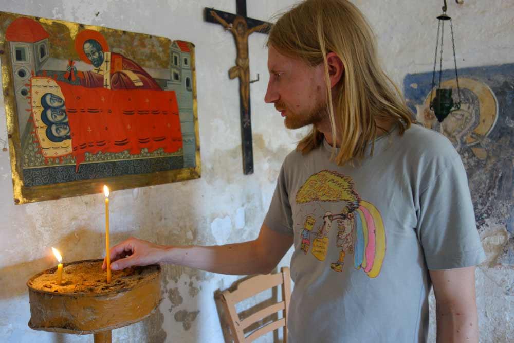 Kirjoittaja sytyttää kynttilän Agios Nikolaoksen kirkossa ikonin edessä.