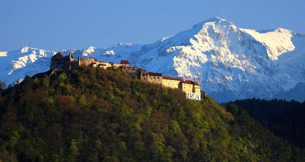 Rasnovin linna vuoren rinteellä. Takana lumihuippuisia vuoria.
