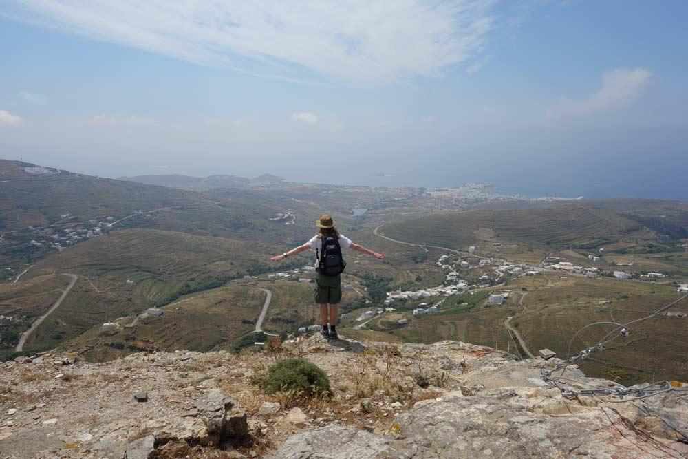 Kirjoittaja selin kädet levitettyinä vuoren huipulla. Näkymä alas vuorelta.