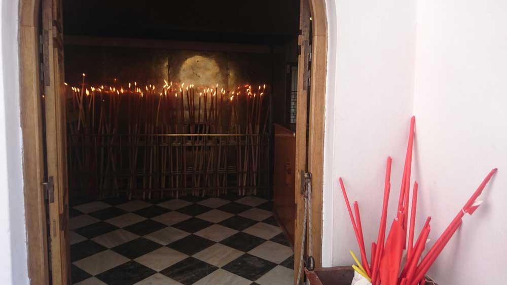 Pääportin luona oleva kappeli, johon pyhiinvaeltajien pitkät kynttilät jätetään palamaan. Oven vieressä pakattuja kynttilöitä.