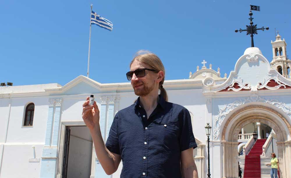 Kirjoittaja kirkon edustalla kädessään pieni pullollinen pyhää vettä