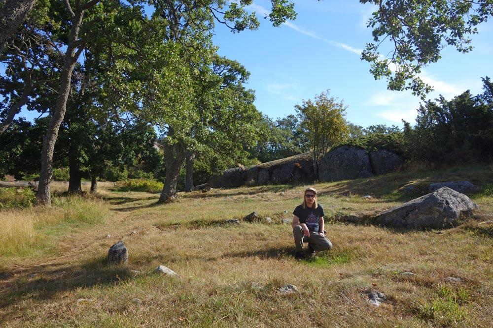 Kirjoittaja Otterböten asuinpaikalla. Maassa näkyvissä asumusten perustuksia. Taustalla isoja tammia ja kallioita.
