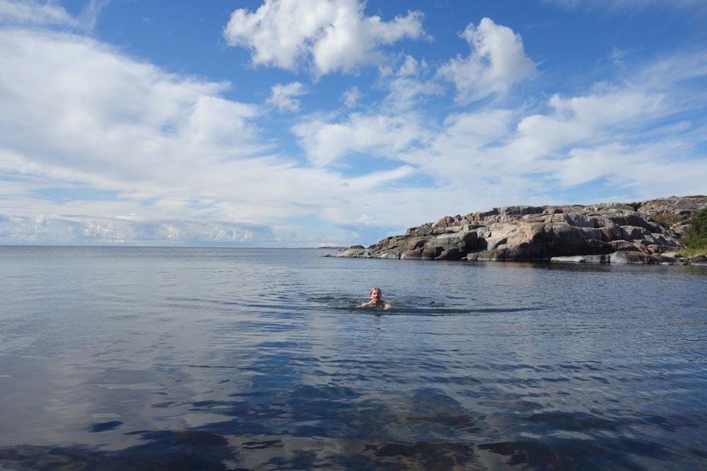Kirjoittaja uimassa meressä. Taustalla avomerta ja kallioita.