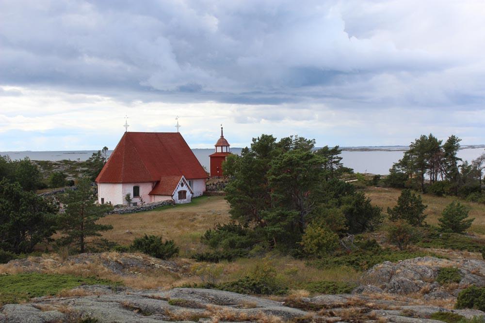 Kökarin kirkko ja kellotapuli. Taustalla meri.