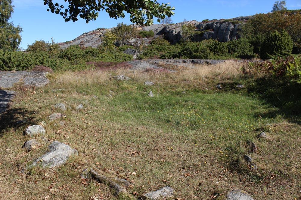 Otterböten pronssikautisen asumuksen perustaa maassa heinikon seassa.