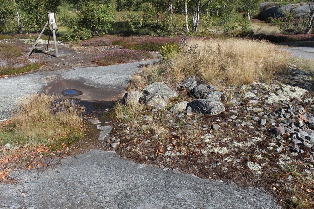 Traanikuoppa. Poltossa halkeilleita kiviä maassa.